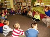 Bibliotekarka Iwona Szczęsna z dziećmi z klasy 0 prowadzi lekcję biblioteczna pod hasłem